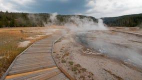 Strandpromenad som buktar runt om den varma våren för varma kaskader i den lägre Geyserhandfatet i den Yellowstone nationalparken Arkivfoto