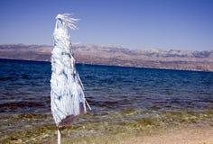 Strandregenschirm durch Ozean Lizenzfreie Stockfotos