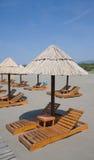 Strandregenschirme und Aufenthaltsraumstühle Lizenzfreie Stockfotografie