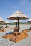 Strandregenschirme und Aufenthaltsraumstühle Stockbild