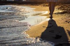 Strandreis - vrouw die op zandig strand lopen die voetafdrukken i verlaten stock afbeelding
