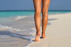 Strandreise - Frau, die auf den Sandstrand herein verlässt Abdrücke geht Lizenzfreie Stockfotos