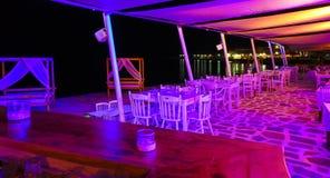 Strandrestaurangen med en stångräknare i förgrunden i lilor färgar på stranden i natt royaltyfri fotografi