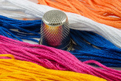 Strands of colored cotton and a thimble Stock Photography