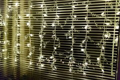 Strands of sparkling little lights in a window. Strands of sparkling little lights hanging in a window in front of a Venetian blind to celebrate Christmas or a Stock Photo