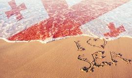 Strandsand, hav och flagga Georgia Jag älskar det Georgia begreppet royaltyfri fotografi