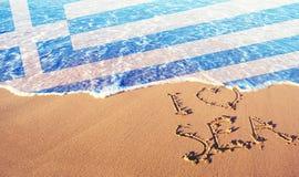Strandsand, hav och flagga Grekland Jag älskar det Grekland begreppet arkivfoto