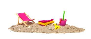 Strandsand mit Stuhl und Spielwaren Lizenzfreie Stockbilder