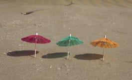 Strandsand och paraply för coctailar Arkivbild