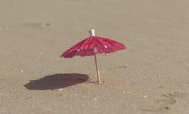 Strandsand och paraply för coctailar Arkivbilder