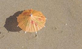 Strandsand och paraply för coctailar Arkivfoton