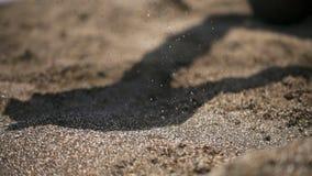 Strandsand som hälls ut ur händerna arkivfilmer