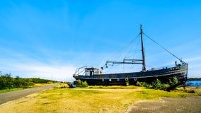 Strandsatt fiskebåt på den Oosterschelde öppningen på den Neeltje Jans ön på barriären för svallvåg för deltaarbetsstorm fotografering för bildbyråer