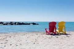 Strandscène met twee kleurrijke adirondackstoelen stock fotografie