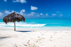Strandschirm auf einem perfekten weißen Strand vor Meer Lizenzfreies Stockfoto