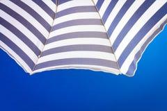 Strandschirm der hohen Auflösung auf Hintergrund des blauen Himmels Lizenzfreies Stockfoto