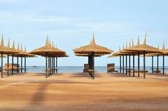 Strandschirme u. Sonnenruhesessel auf dem Strand Stockbilder
