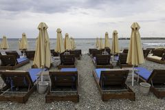 Strandschirme und leere Klubsessel an einem bewölkten Tag Platamonas stockfoto