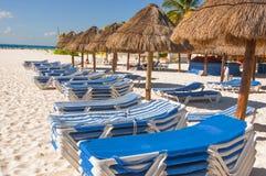 Strandschuilplaatsen en stoelen in de zon op een strand Royalty-vrije Stock Afbeelding