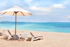 Strandsidan vilar stolar och paraplyer på sanden fotografering för bildbyråer