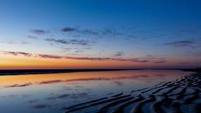 Strandsolnedgång med blå och orange himmel arkivbilder