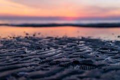 Strandsolnedgångfotspår på sanden arkivfoto