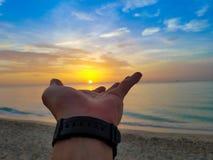 Strandsoluppgång med en hand av guden på solen Arkivbilder