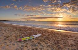 Strandsoluppgång och paddleboard på shoreline Royaltyfria Bilder