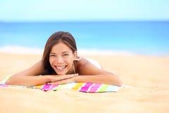 Strandsommerfrau, die das Sonnenlächeln genießend ein Sonnenbad nimmt Stockbild