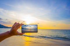 Strandsonnenuntergang mit intelligentem Telefonschuß Lizenzfreies Stockfoto