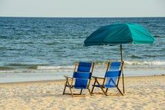 Strandstühle, die den Ozean übersehen Stockbilder