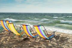 Strandstühle, die ein windiges Meer gegenüberstellen stockfotos