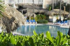 Strandstühle im Swimmingpool im tropischen Hotel nehmen Zuflucht Entspannende Zeit im Pool Lizenzfreies Stockbild