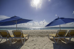 Strandstühle mit Regenschirmen in der Sonne auf einem Strand Lizenzfreies Stockbild