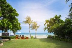 Strandstühle mit Tabelle auf dem Strand unter der Palme vor dem Meer Schauen Sie voran zum Meer Kann Gebrauch als Hintergrund von Stockbild