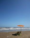 Strandstühle und bunter Regenschirm Stockfotografie