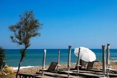 Strandstühle und ein Sonnenschirm Lizenzfreies Stockfoto
