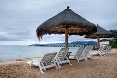 Strandstühle und mit Stroh gedeckte Regenschirme Lizenzfreie Stockfotos