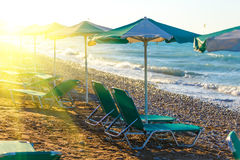Strandstühle und -regenschirm auf dem Ufer eines kieseligen Strandes Griechenland Rhodos mit Sonnenaufflackern-Dämmerungszeit stockbild