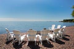 Strandstühle vereinbarten in einem Halbrund auf dem Ufer von See Super Lizenzfreie Stockbilder
