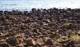 Strandstenen en water op achtergrond stock afbeeldingen