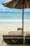 Strandstol och paraply Arkivfoto