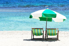Strandstol och paraply på stranden Royaltyfri Fotografi