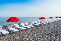 Strandstolar eller sängar och röda paraplyer för sol på stranden Arkivbild