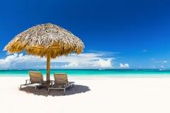 Strandstolar med paraplyet och härlig sand sätter på land Royaltyfria Bilder