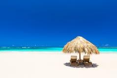 Strandstolar med paraplyet och härlig sand sätter på land Arkivbilder