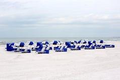 Strandstolar och paraplyer Arkivfoto