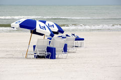 Strandstolar och paraplyer Fotografering för Bildbyråer
