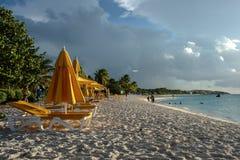 Strandstolar och paraplyer på solnedgången, östlig stimfjärd, Anguilla, brittiska västra Indies, BWI som är karibisk Royaltyfria Bilder