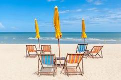 Strandstolar och solparaplyer på den vita sanden sätter på land med clea Royaltyfri Fotografi